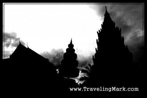 Silhouettes of Wat Preah Prom Rath Against Cloudy Skies