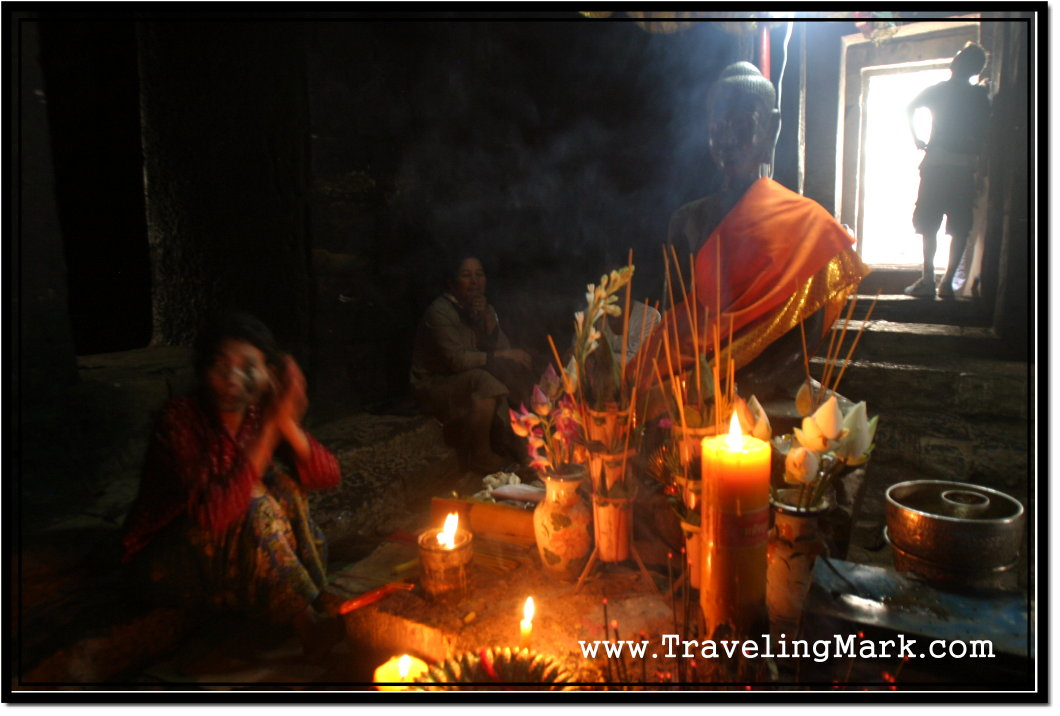 Photo: Cambodian Woman Praying Before the Statue of Buddha at Bayon Temple